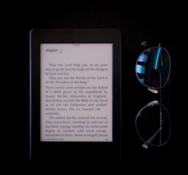 Image of an e-reader and a pair of reading glasses